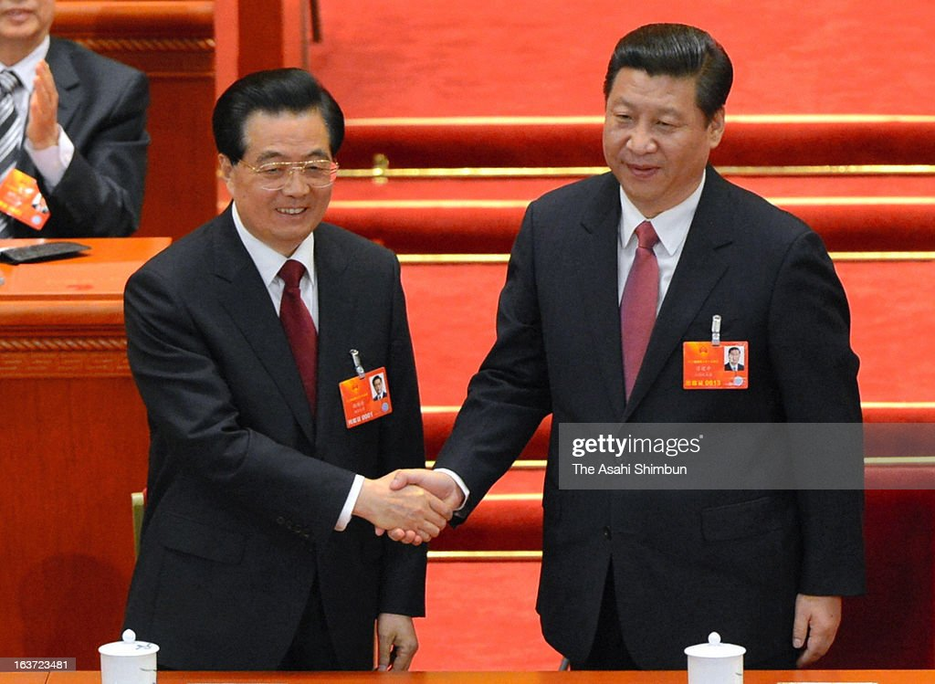 China's newly-elected President Xi Jinping (R) shakes hands with former President Hu Jintao at the fourth plenary meeting of the National People's Congress at the Great Hall of the People on March 14, 2013 in Beijing, China.
