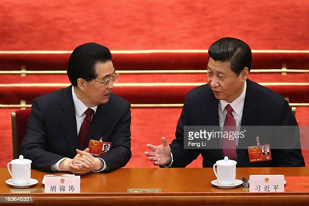China's newlyelected President Xi Jinping talks with former President Hu Jintao during the fourth plenary meeting of the National People's Congress...