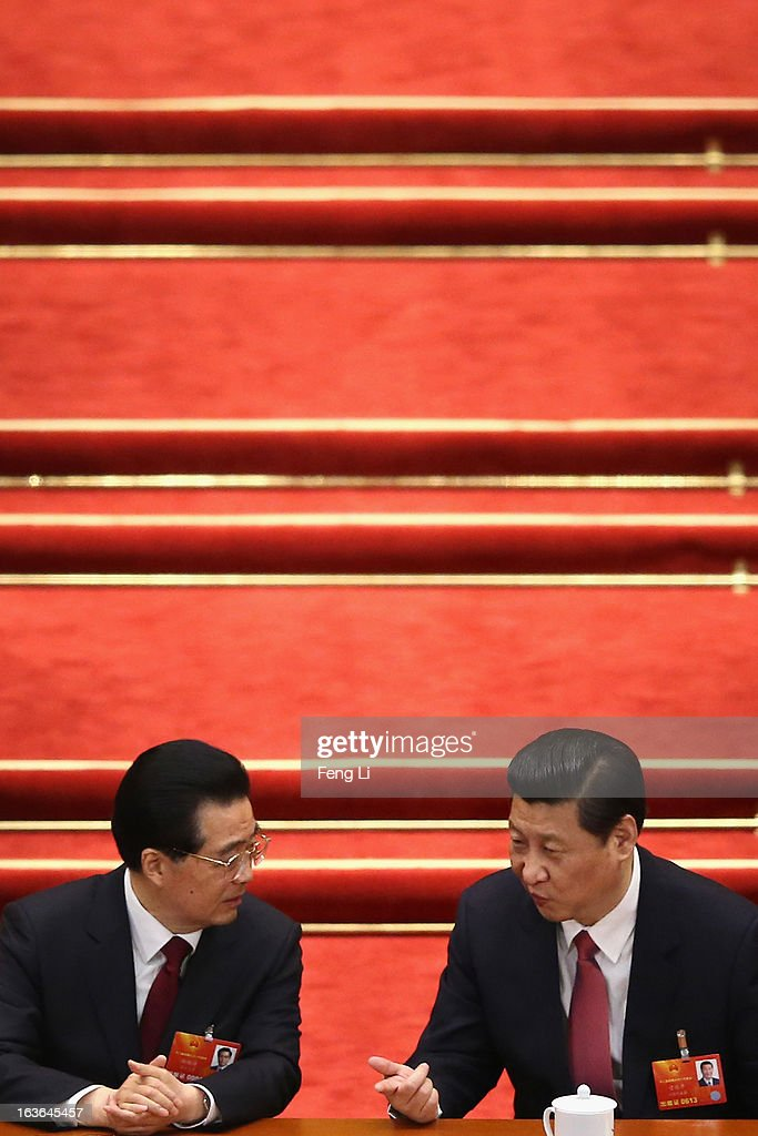 China's newly-elected President Xi Jinping (R) talks with former President Hu Jintao (L) during the fourth plenary meeting of the National People's Congress at the Great Hall of the People on March 14, 2013 in Beijing, China. Xi Jinping, general secretary of the Communist Party of China Central Committee, was elected President of the People's Republic of China and Chairman of the Central Military Commission on Thursday.