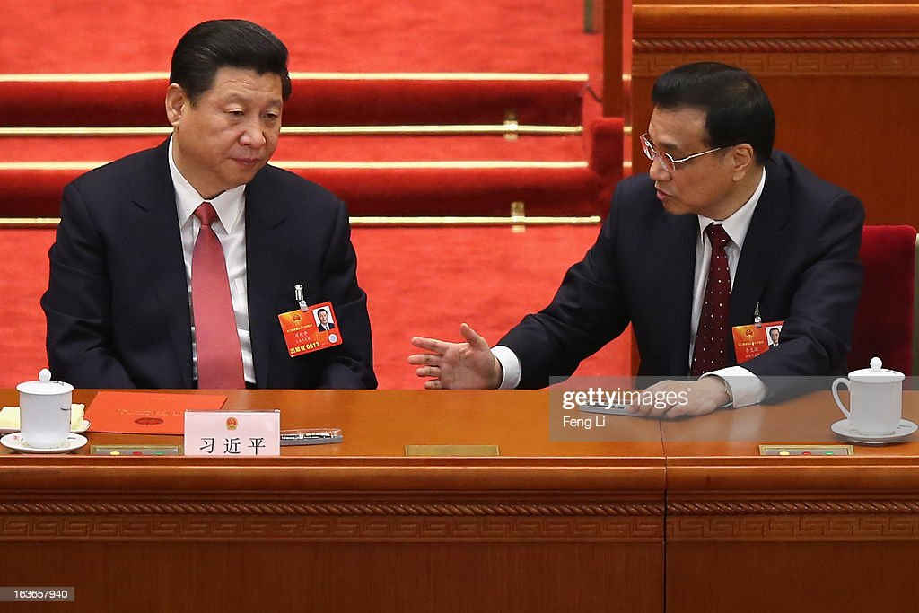China's newly-elected President Xi Jinping (L) talks with incoming-Premier Li Keqiang (R) during the fourth plenary meeting of the National People's Congress at the Great Hall of the People on March 14, 2013 in Beijing, China. Xi Jinping, general secretary of the Communist Party of China Central Committee, was elected President of the People's Republic of China and Chairman of the Central Military Commission on Thursday.