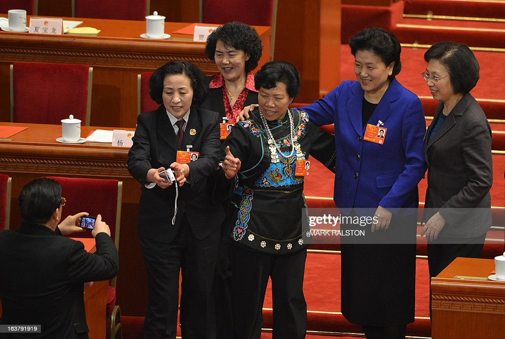 China's newly-elected Vice Premier Liu Yandong (2nd R) stands with women delegates during the election of the new vice premiers, foreign and defence ministers of China during the 12th National People's Congress (NPC) in the Great Hall of the People in Beijing on March 16, 2013. China's parliament named Xi Jinping as president on March 15 four months after he took charge of the Communist Party with pledges of reform that have raised hopes but so far yielded little change. AFP PHOTO / Mark RALSTON