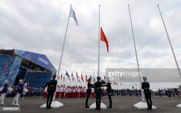 China's Olympic delegation members attend the raising of their national flag at the Olympic Park's Medal Plaza two days prior to the start of the...