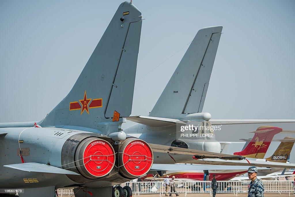 A China's People Liberation Army soldier stands guard next to planes displayed during the 9th China International Aviation and Aerospace Exhibition...
