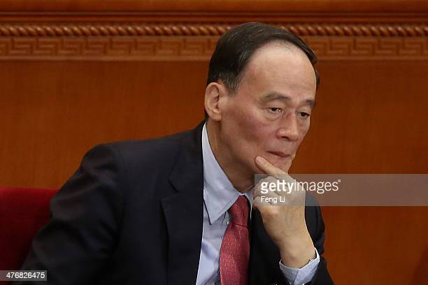 China's Politburo Standing Committee member Wang Qishan attends the opening session of the National People's Congress at the Great Hall of the People...
