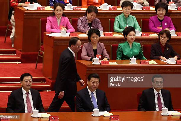 China's Politburo Standing Committee member Wang Qishan walks past President Xi Jinping and Premier Li Keqiang after speaking during the opening...