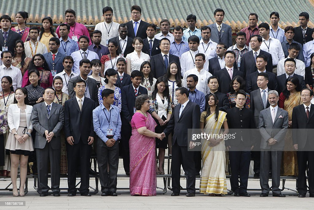 China's Premier Li Keqiang (centre R-in black) shakes hands with Nita Chowdhury (centre L-in pink), secretary of the Ministry of Youth Affairs and Sports of India, after a group photo during a meeting with members of an Indian youth delegation at the Zhongnanhai compound in Beijing on May 15, 2013. The visit by the delegation happens ahead of a visit to India by Li later this month. AFP PHOTO / POOL / Jason Lee