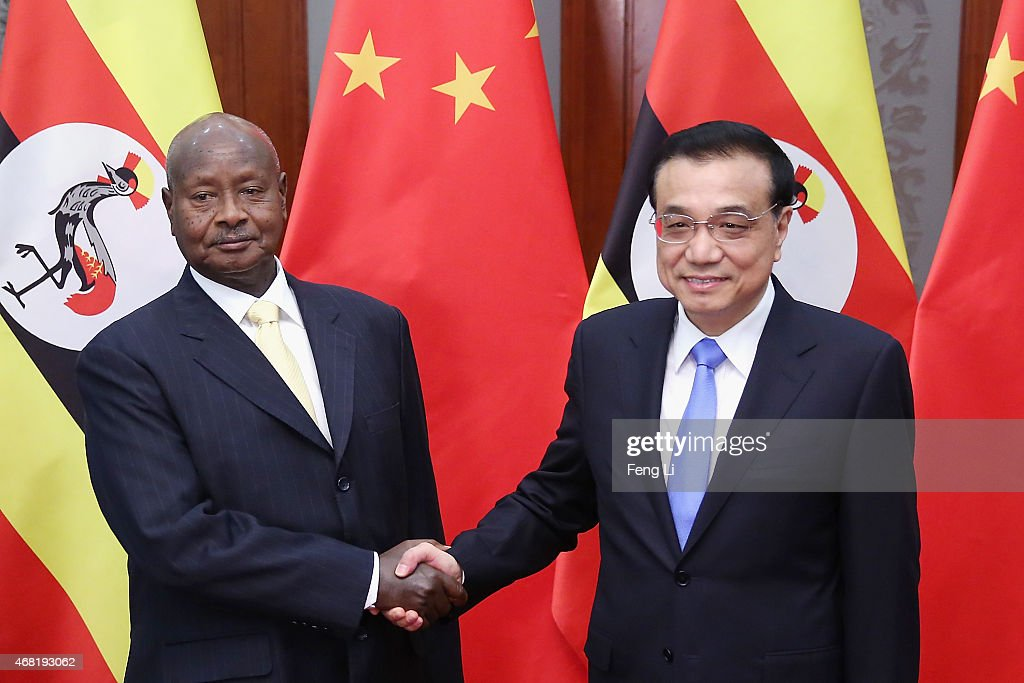 China's Premier Li Keqiang shakes hands with Ugandan President Yoweri Kaguta Museveni at the Great Hall of the People on March 31 2015 in Beijing...