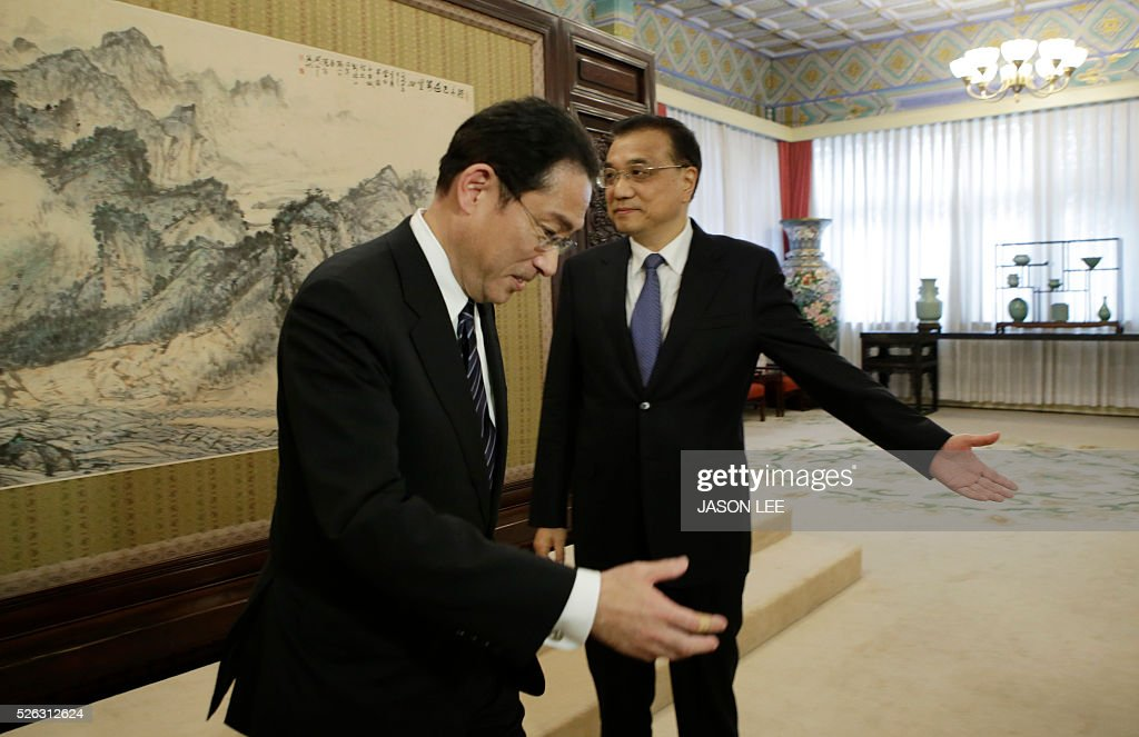 China's Premier Li Keqiang (R) shows the way to Japanese Foreign Minister Fumio Kishida during a meeting at Zhongnanhai in Beijing on April 30, 2016. / AFP / pool / JASON LEE
