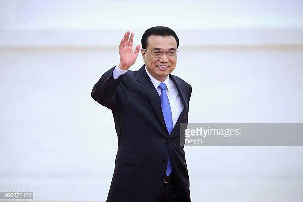 China's Premier Li Keqiang waves as arriving the annual news conference following the closing session of the National People's Congress at the Great...