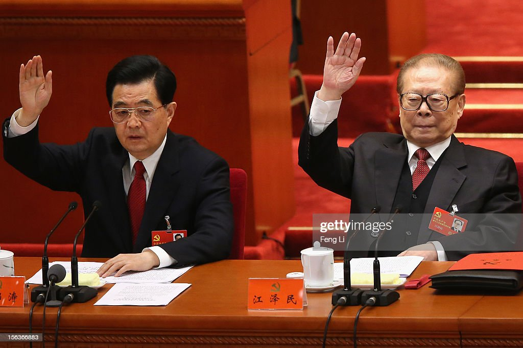 China's President Hu Jintao and former President Jiang Zemin raise their hands as they take a vote during the closing session of the 18th National...