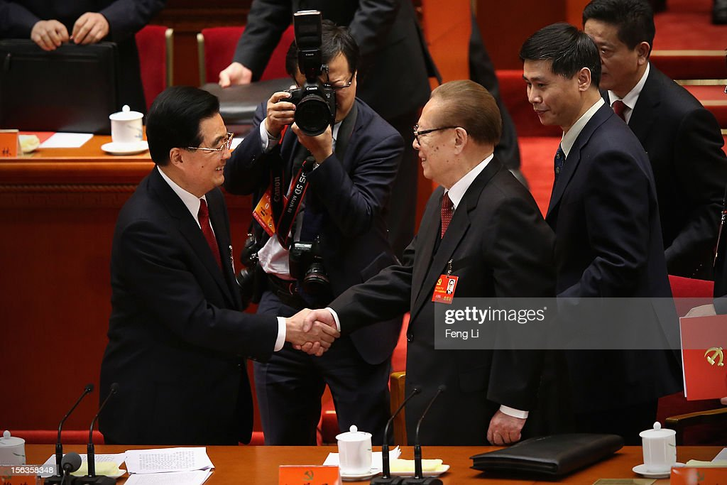 China's President Hu Jintao and former President Jiang Zemin shake hands after the closing session of the 18th National Congress of the Communist...