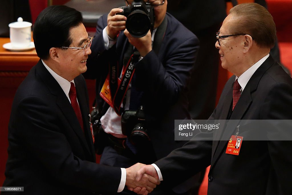 China's President Hu Jintao (L) and former President Jiang Zemin (R) shake hands after the closing session of the 18th National Congress of the Communist Party of China (CPC) at the Great Hall of the People on November 14, 2012 in Beijing, China. Members of the Standing Committee of the Political Bureau of the new CPC Central Committee will meet with journalists on November 15, 2012.
