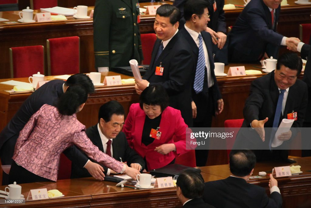 China's President Hu Jintao signs autographs for female delegates as Chinese Vice President Xi Jinping looks behind them after the second plenary...