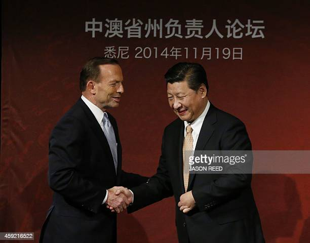 China's President Xi Jinping and Australia's Prime Minister Tony Abbott shake hands on stage after they both addressed the AustraliaChina state and...