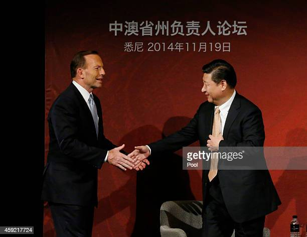 China's President Xi Jinping and Australia's Prime Minister Tony Abbott shake hands on stage after they both addressed the Australia China state and...