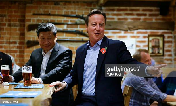 China's President Xi Jinping and Britain's Prime Minister David Cameron drink a pint of beer during a visit to the The Plough pub on October 22 2015...