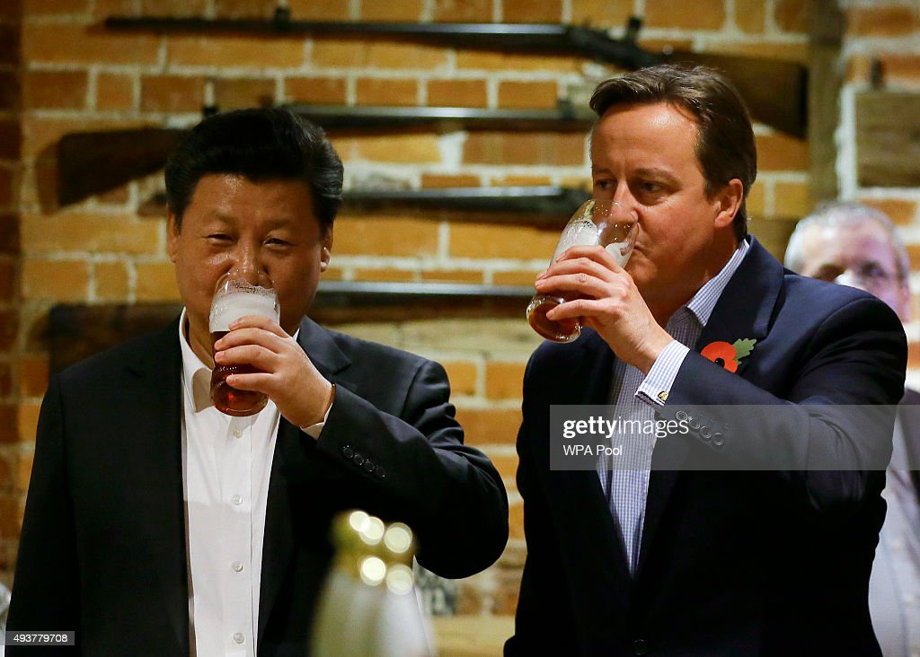 China's President Xi Jinping and Britain's Prime Minister David Cameron drink a pint of beer during a visit to the The Plough pub on October 22, 2015 in Princes Risborough, England. The President of the People's Republic of China, Mr Xi Jinping and his wife, Madame Peng Liyuan, are paying a State Visit to the United Kingdom as guests of The Queen. They will stay at Buckingham Palace and undertake engagements in London and Manchester. The last state visit paid by a Chinese President to the UK was Hu Jintao in 2005.