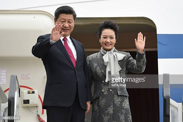 China's President Xi Jinping and his wife Peng Liyuan wave as they board an Air China plane at Manchester airport on October 23 2015 in Manchester...