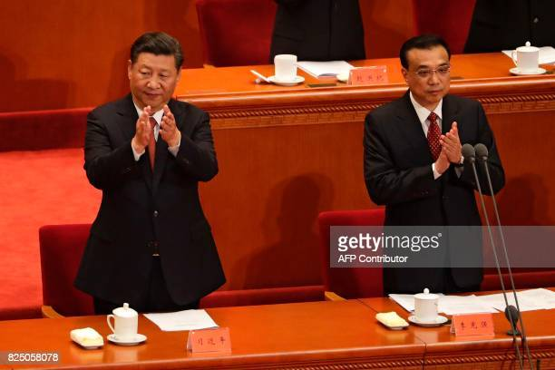 China's President Xi Jinping and Premier Li Keqiang applaud during a ceremony to commemorate the 90th anniversary of the founding of the People's...