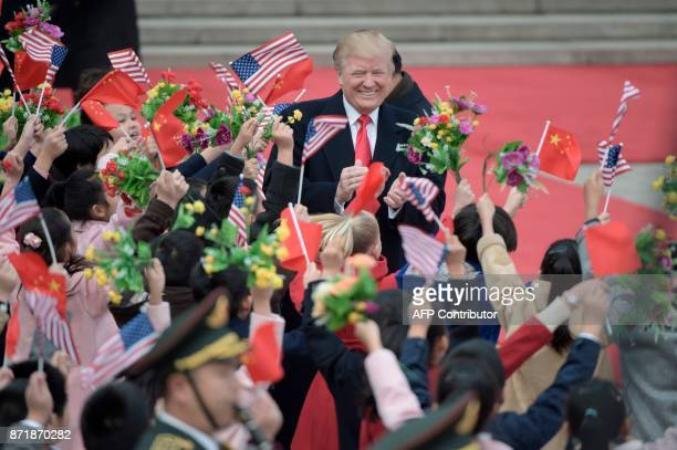 TOPSHOT China's President Xi Jinping and US President Donald Trump attend a welcome ceremony at the Great Hall of the People in Beijing on November 9...
