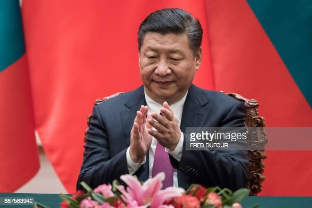 China's President Xi Jinping applauds during a signing ceremony with Maldives' President Abdulla Yameen at the Great Hall of the People in Beijing on...