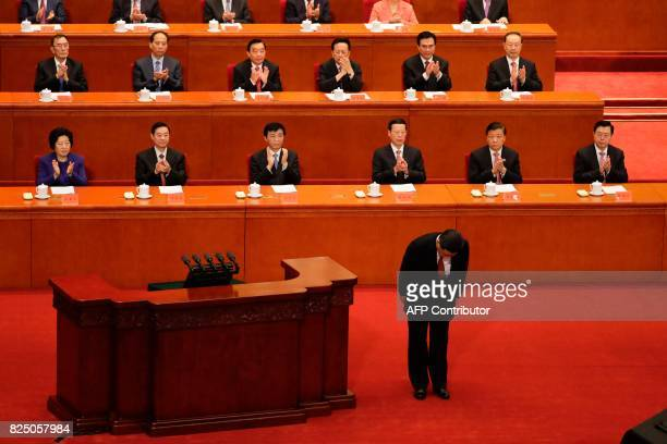 China's President Xi Jinping bows before delivering a speech at a ceremony to commemorate the 90th anniversary of the founding of the People's...