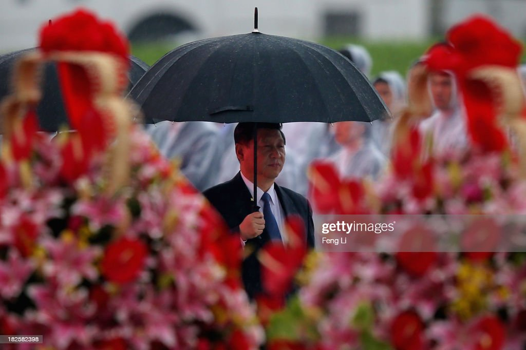 China's President Xi Jinping hold umbrella as he arrive for a tribute ceremony marking the 64th anniversary of the founding of the People's Republic of China at Tiananmen Square on October 1, 2013 in Beijing, China. On October 1, 1949, Chinese leader Mao Zedong stood at the Tiananmen Rostrum to declare the founding of the People's Republic of China.