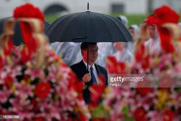 China's President Xi Jinping hold umbrella as he arrive for a tribute ceremony marking the 64th anniversary of the founding of the People's Republic...