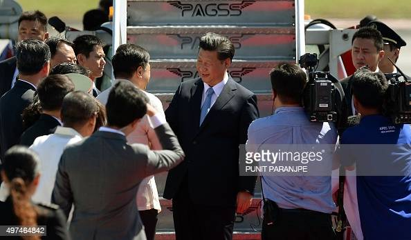 China's President Xi Jinping is surrounded by delegates and the media upon his arrival at the international airport ahead of the AsiaPacific Economic...