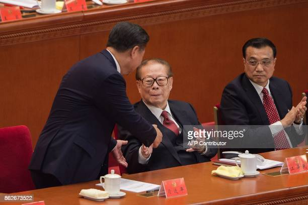 China's President Xi Jinping shakes hands at the end of his speech with former president Jiang Zemin as Premier Li Keqiang looks on during the...