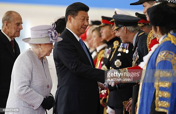 China's President Xi Jinping shakes hands with British officials and dignitaries flanked by Britain's Queen Elizabeth II at the royal pavilion on...