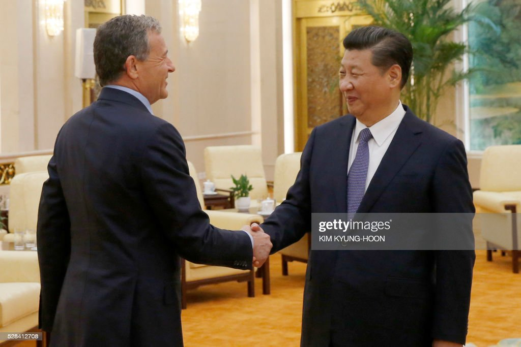 China's President Xi Jinping (R) shakes hands with Chief Executive Officer of Disney Bob Iger as they meet at the Great Hall of the People in Beijing on May 5, 2016. / AFP / REUTERS / KIM