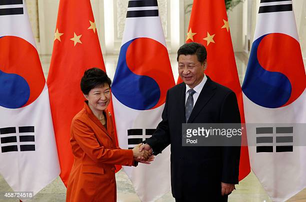China's President Xi Jinping shakes hands with South Korea's President Park Geunhye in front of Chinese and South Korean national flags during a...