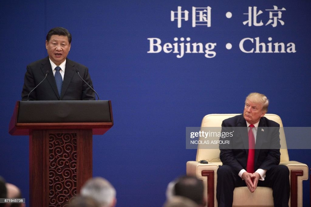 China's President Xi Jinping (L) speaks next to US President Donald Trump during a business leaders event at the Great Hall of the People in Beijing on November 9, 2017. Donald Trump urged Chinese leader Xi Jinping to work 'hard' and act fast to help resolve the North Korean nuclear crisis, during their meeting in Beijing on November 9, warning that 'time is quickly running out'. / AFP PHOTO / Nicolas ASFOURI