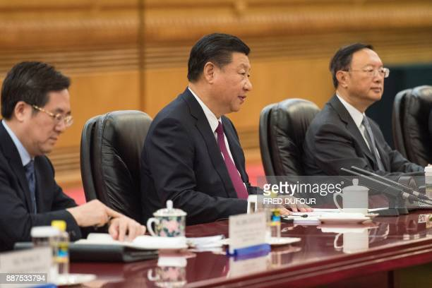 China's President Xi Jinping speaks to Maldives' President Abdulla Yameen during a meeting at the Great Hall of the People in Beijing on December 7...