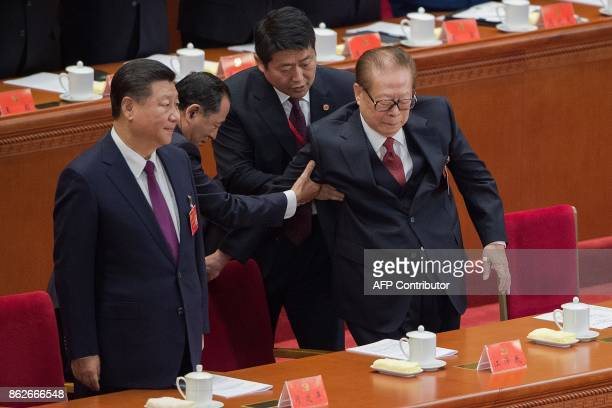 China's President Xi Jinping stands next to former president Jiang Zemin as he is assisted by two helpers during the opening of the 19th Communist...