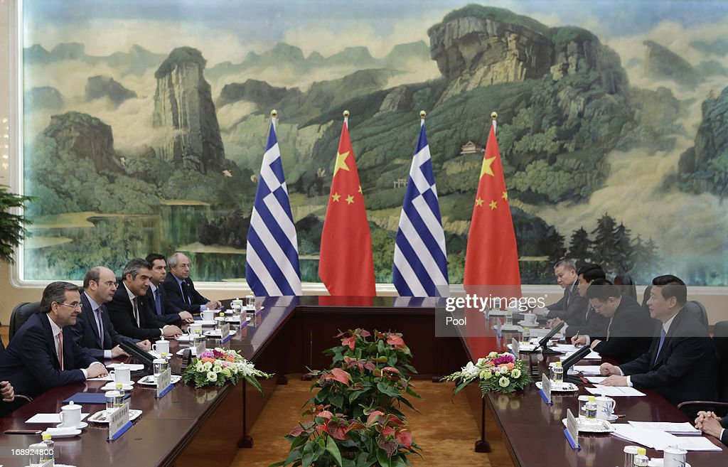 China's President Xi Jinping ( R) talks with Greece's Prime Minister Antonis Samaras (L) during a meeting at the Great Hall of the People in Beijing, May 17, 2013. Greece is willing to roll out the 'red carpet' according to Samaras if China was willing to invest in the Greek economy.
