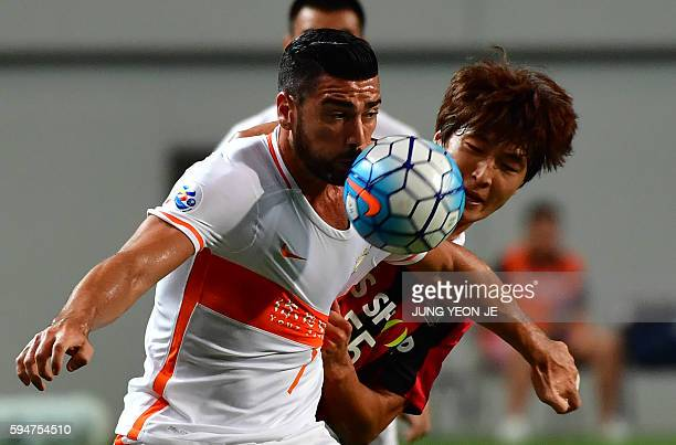 China's Shandong Luneng FC forward Graziano Pelle fights for the ball with South Korea's FC Seoul defender Kwak TaeHwi during their quarterfinal...