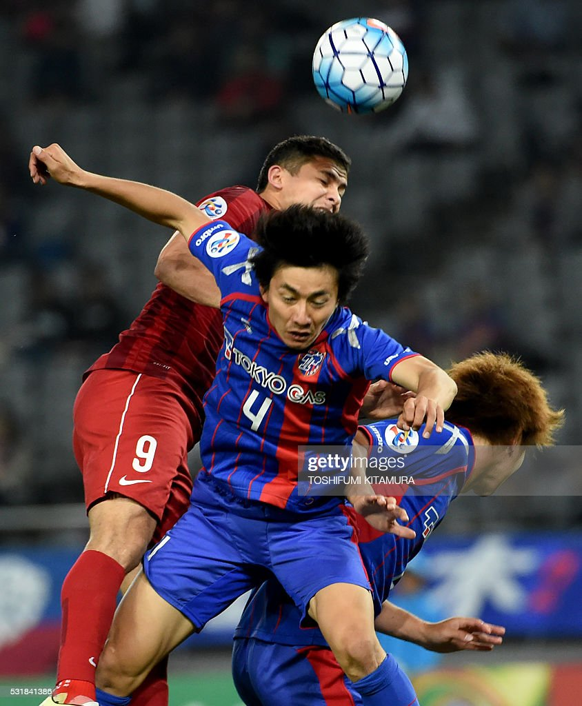 China's Shanghai SPIG forward Elkeson de Oliveira Cardoso (L) fights for the ball with Japan's FC Tokyo midfielder Hideto Takahashi (C) during the AFC champions league round of 16 first match in Tokyo on May 17, 2016. / AFP / TOSHIFUMI