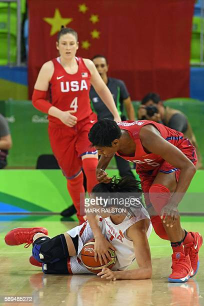 China's small forward Shao Ting falls next to USA's small forward Angel Mccoughtry and USA's guard Lindsay Whalen during a Women's round Group B...