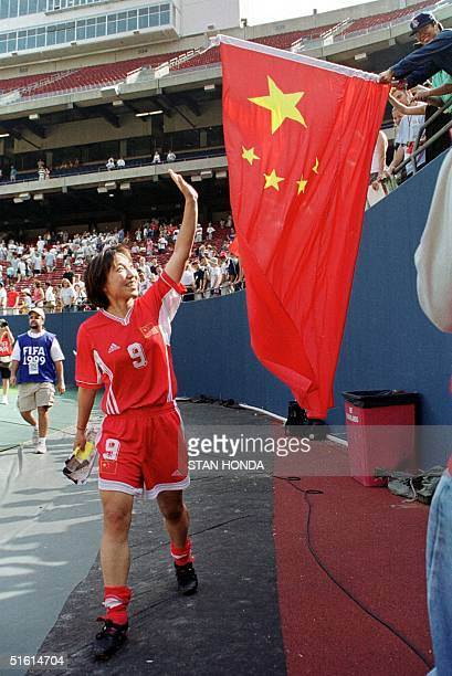 China's Sun Wen walks past a Chinese flag and waves to the crowd after her team beat Australia 31 in a Women's World Cup match 26 June 1999 at Giants...