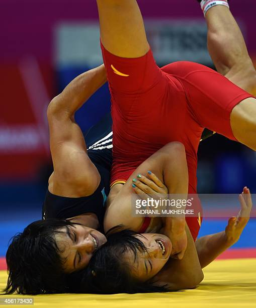 China's Sun Yanan flips Kazakhstan's Tatyana Amanzhol during the women's freestyle wrestling 48 kg event of the 2014 Asian Games at the Dowon...