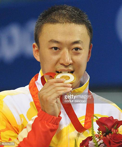 China's table tennis player Ma Lin celebrates with the gold medal after winning the men's table tennis singles final at the 2008 Beijing Olympic...