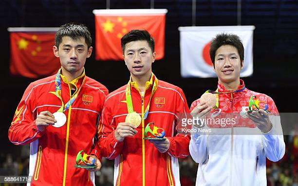 China's table tennis singles gold medalist Ma Long and silver medalist Zhang Jike stand alongside Japan's bronze medalist Jun Mizutani on the podium...