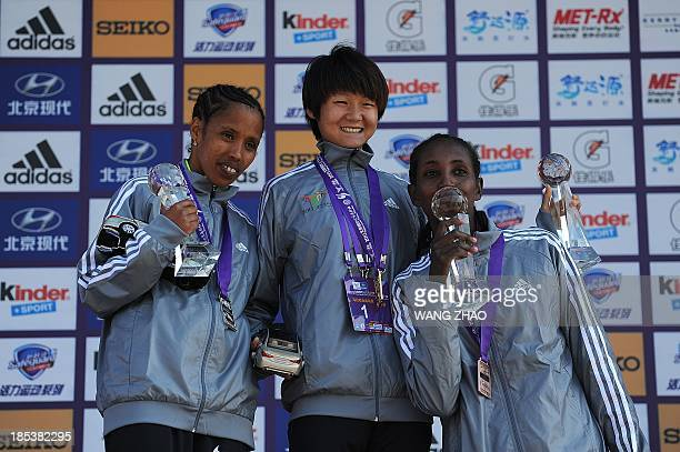 China's Tola Zhang Yingying celebrates with second placed Ethiopia's Makda Harun Haji and third placed Ethiopia's Yeshimebet Tadesse Bifa on the...