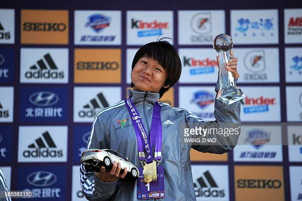 China's Tola Zhang Yingying poses with her medal on the podium as she attends the presentation ceremony after winning the woman's portion of the...