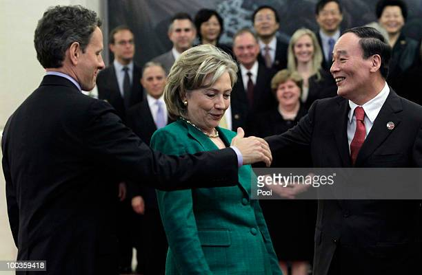 China's Vice Premier Wang Qishan and US Treasury Secretary Timothy Geithner try to shake hands while US Secretary of State Hillary Clinton stands in...