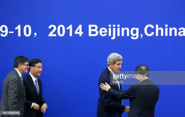 China's Vice Premier Wang Yang and US Secretary of the Treasury Jack Lew look at US Secretary of State John Kerry shaking hands with China's State...