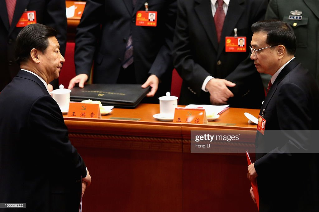 China's Vice President Xi Jinping (L) and China's Vice-Premier Li Keqiang (R) leave their seats after the closing session of the 18th National Congress of the Communist Party of China (CPC) at the Great Hall of the People on November 14, 2012 in Beijing, China. Members of the Standing Committee of the Political Bureau of the new CPC Central Committee will meet with journalists on November 15, 2012.