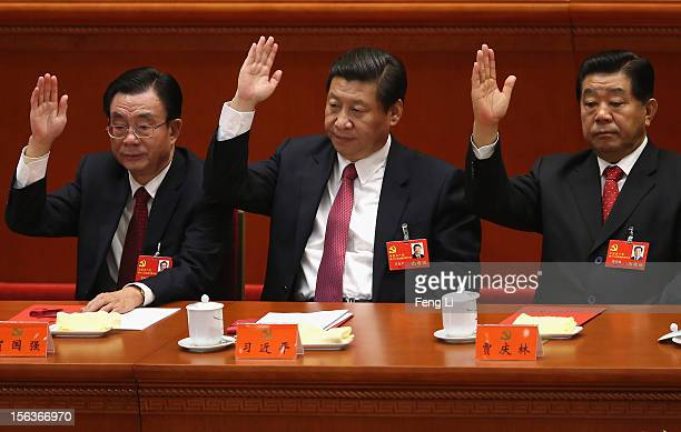 China's Vice President Xi Jinping raise his hand as he takes a vote during the closing session of the 18th National Congress of the Communist Party...